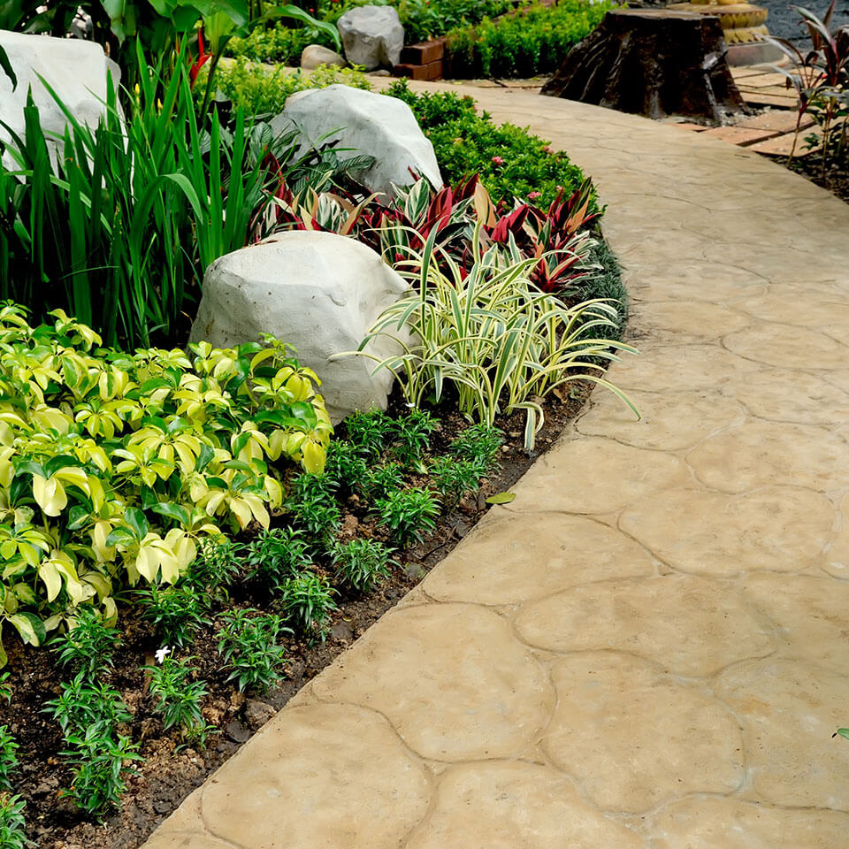 Hardscape and landscape design with textured stone walkway, decorative rocks, and garden