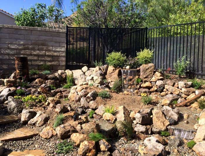 hardscaping with natural stones and steps towards a water fall